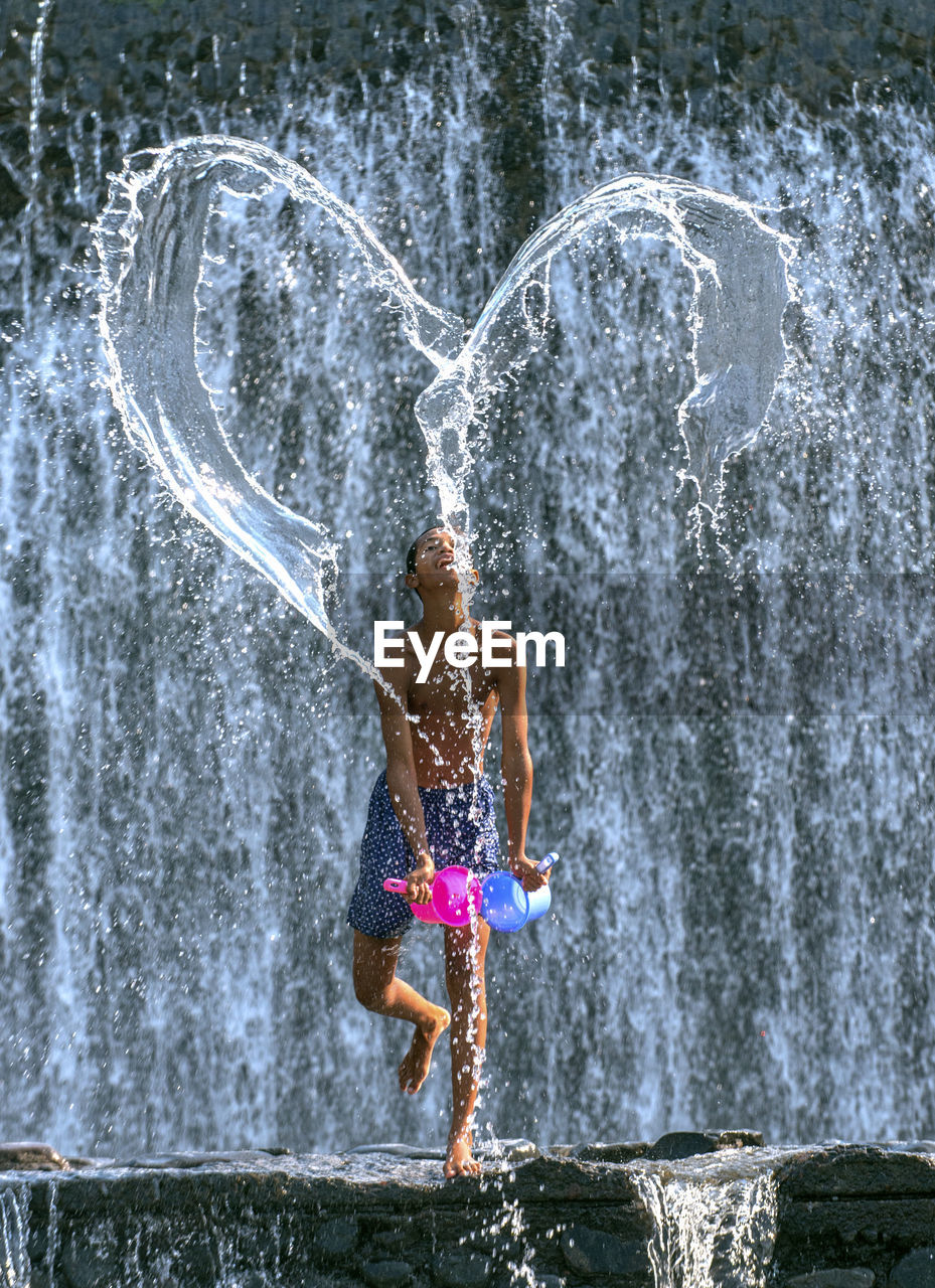Shirtless Man Throwing Water In Heart Shape Against Waterfall