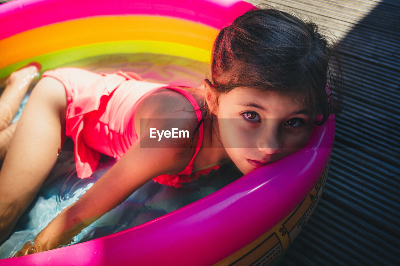 Portrait Of Cute Girl Lying In Colorful Wading Pool