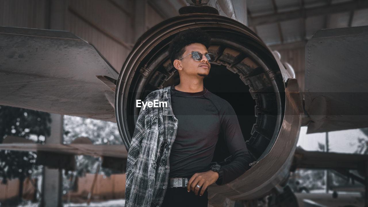 Young man wearing sunglasses standing at aircraft hangar