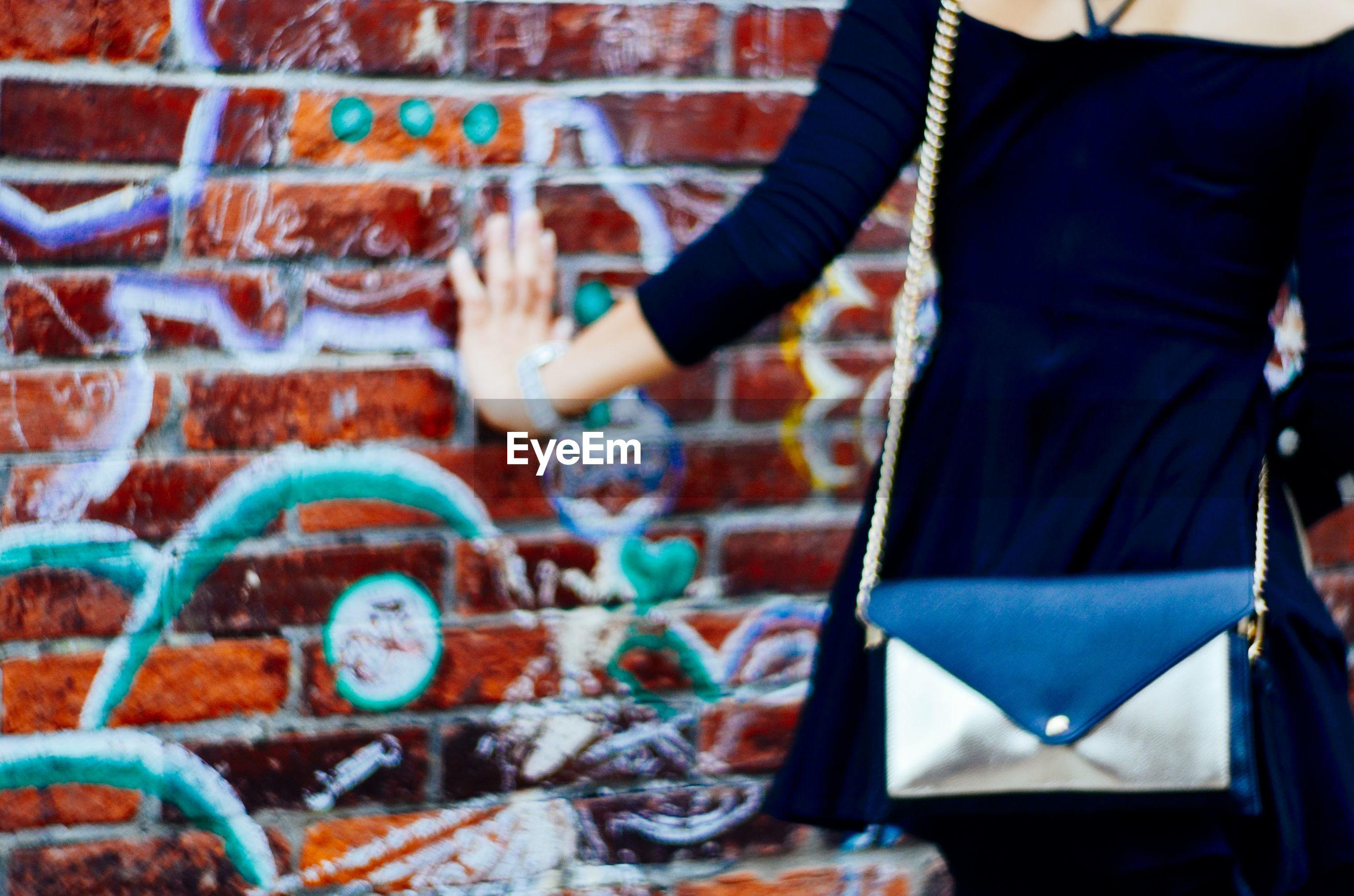 Midsection of woman touching graffiti wall