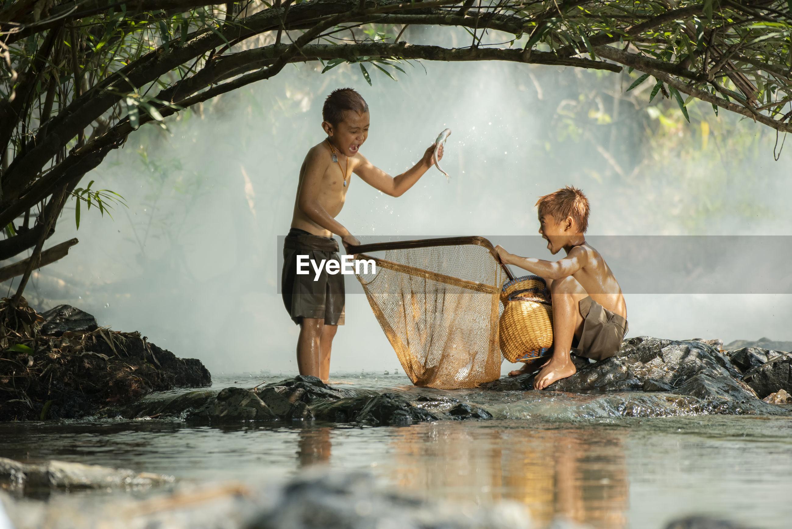 Boys catching fish in lake