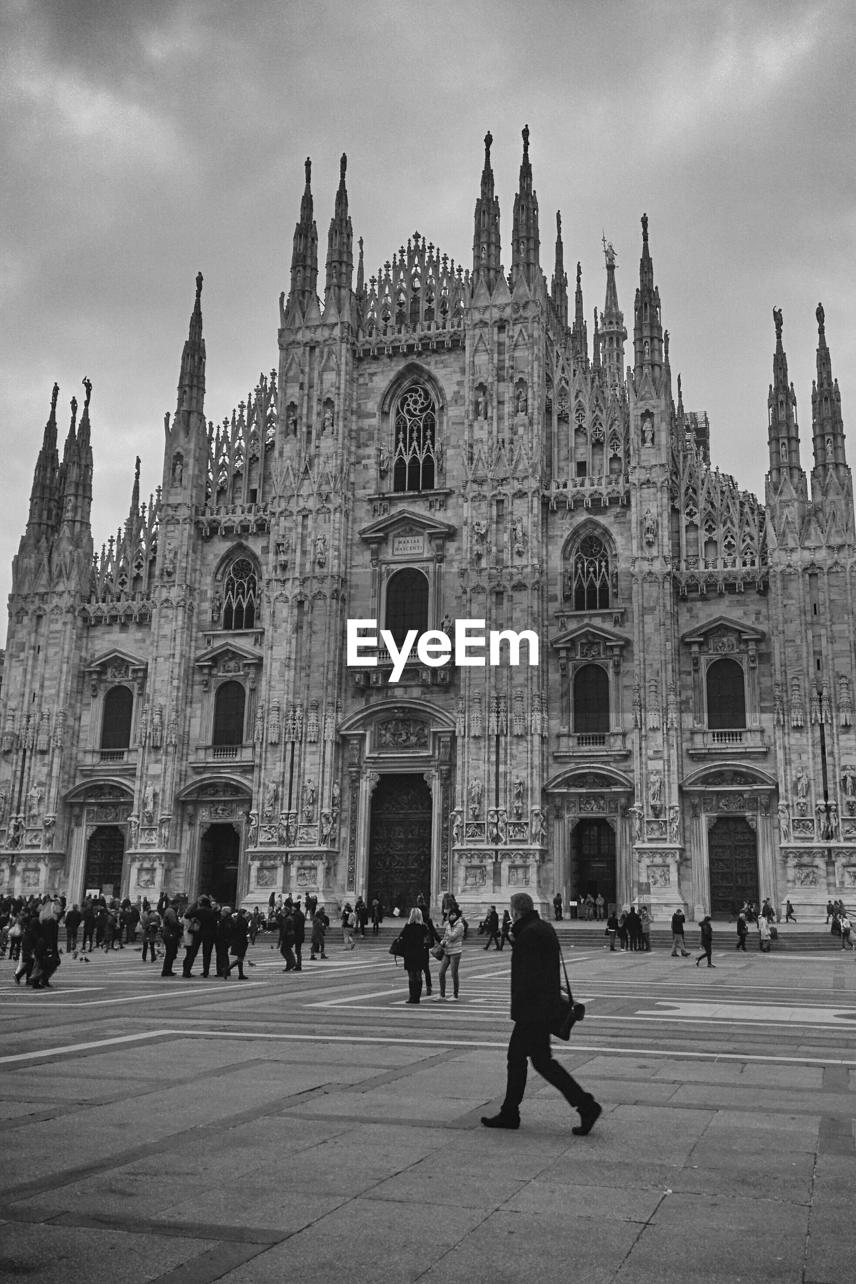 People at milan cathedral against cloudy sky