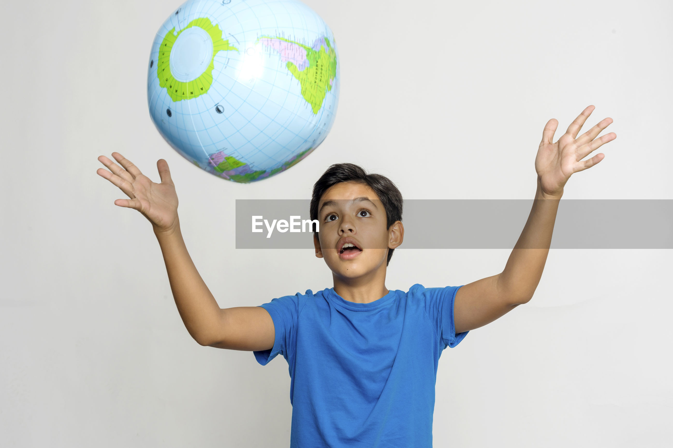 Boy catching globe while standing against white background