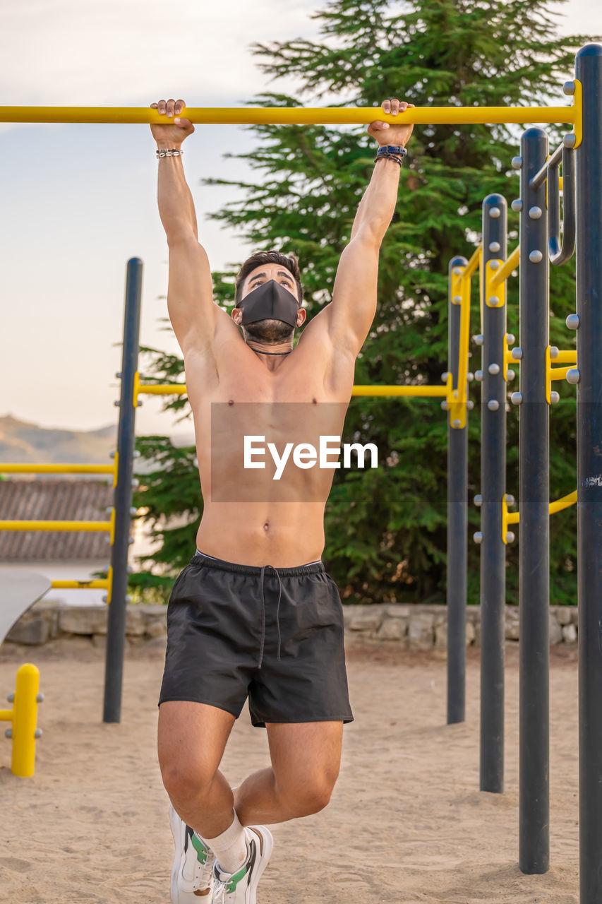 Young man wearing flu mask exercising outdoors