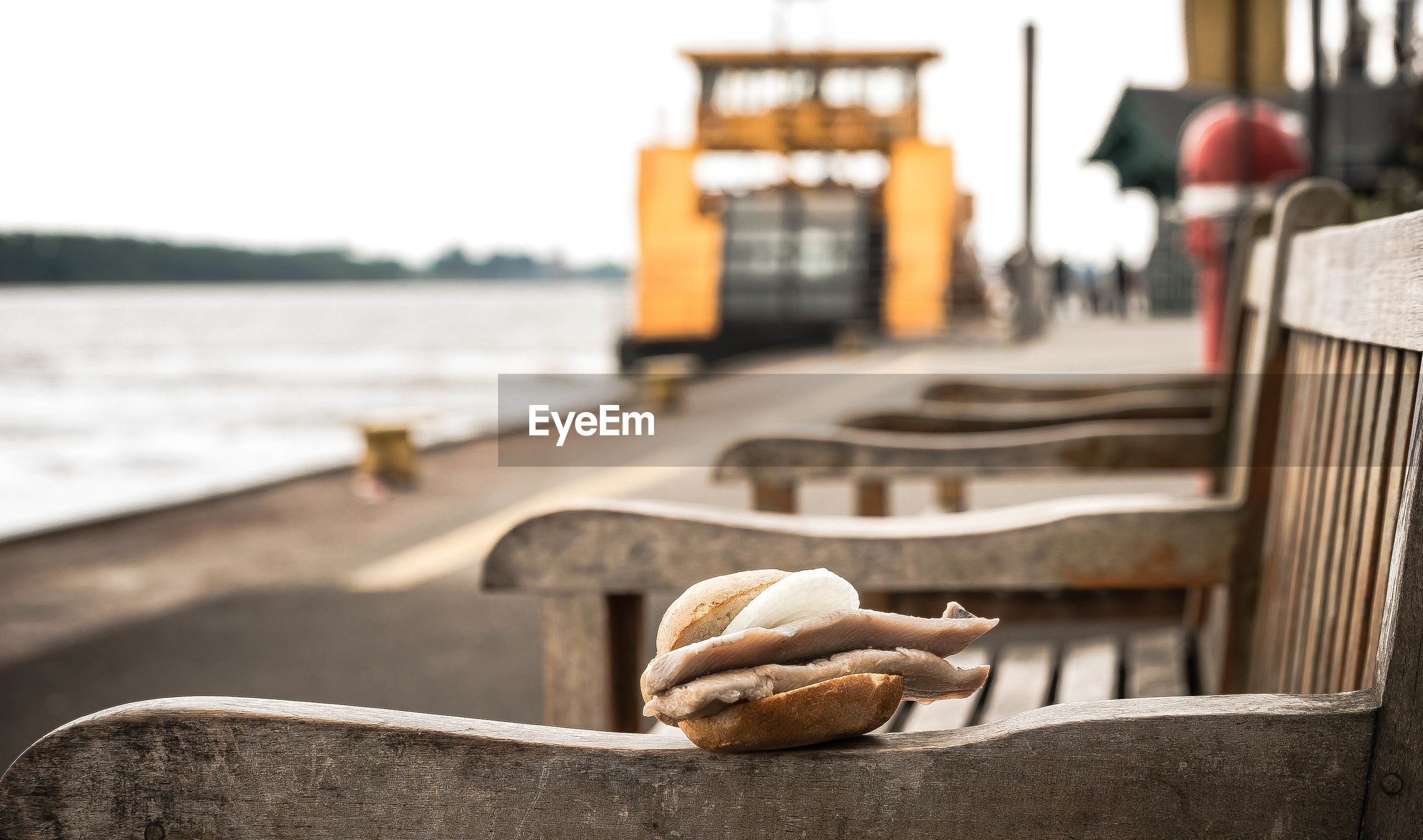 Close-up of sandwich on bench by river against sky