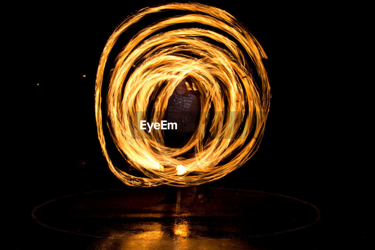 motion, long exposure, illuminated, burning, glowing, fire - natural phenomenon, fire, blurred motion, spinning, night, orange color, circle, heat - temperature, nature, arts culture and entertainment, wire wool, geometric shape, shape, one person, skill, dark, black background, light, firework display