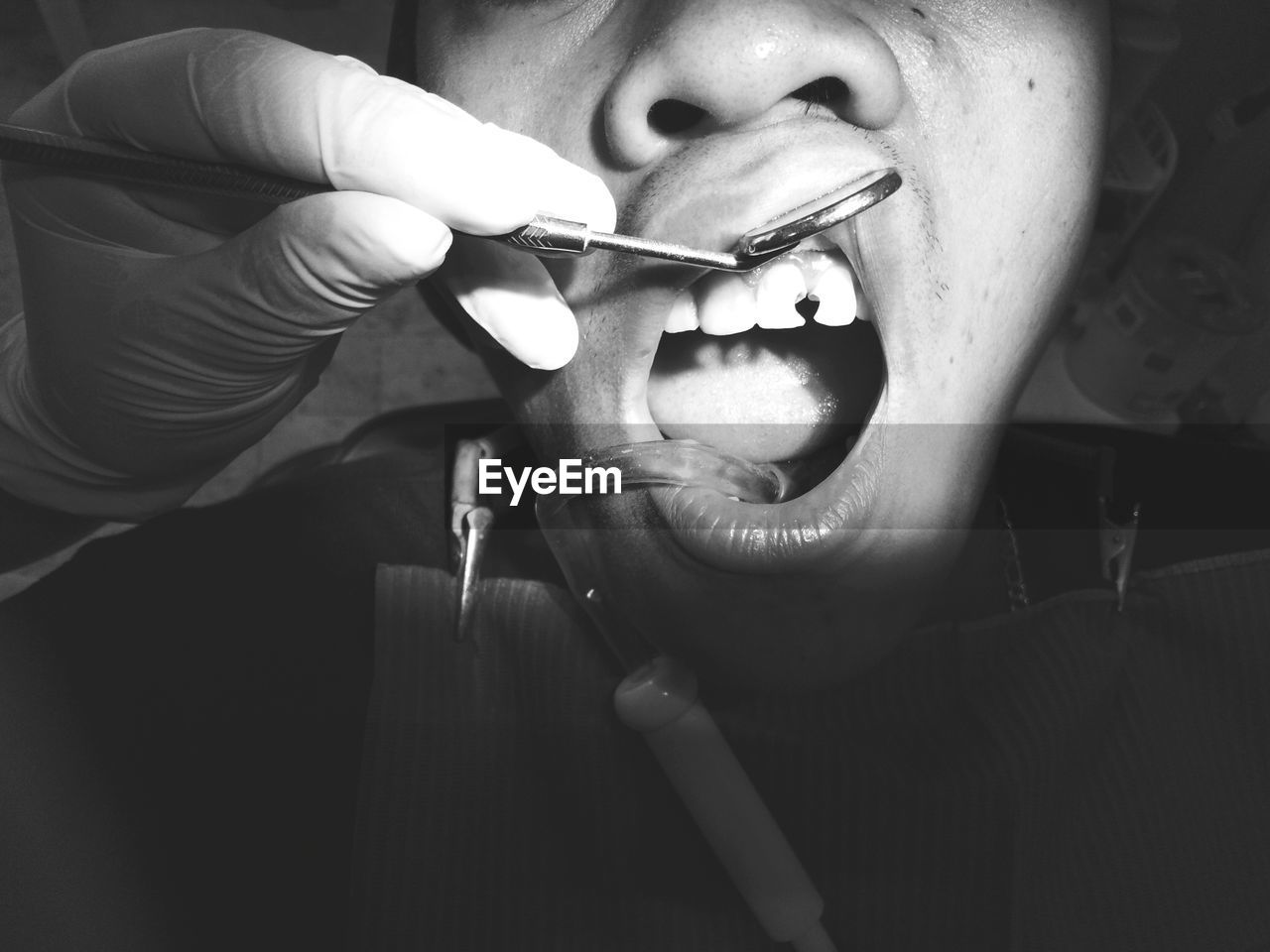 Cropped Hand Of Dentist Operating Patient Teeth In Clinic