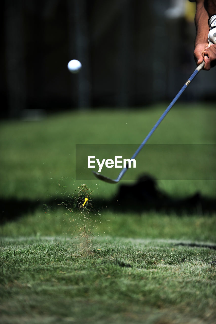 Cropped Hands Of Man Playing Golf On Course