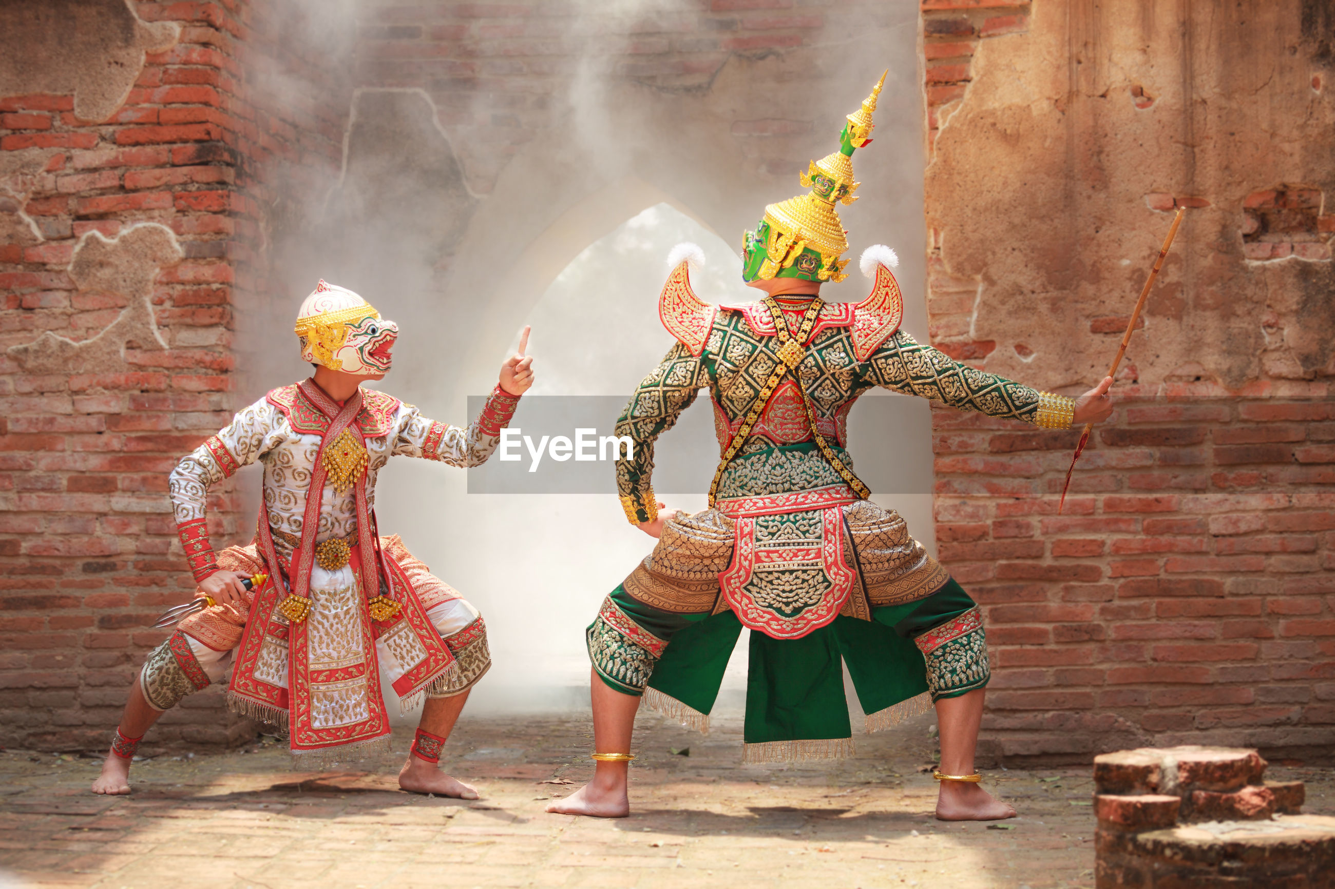 Male performers wearing traditional clothing while acting on stage