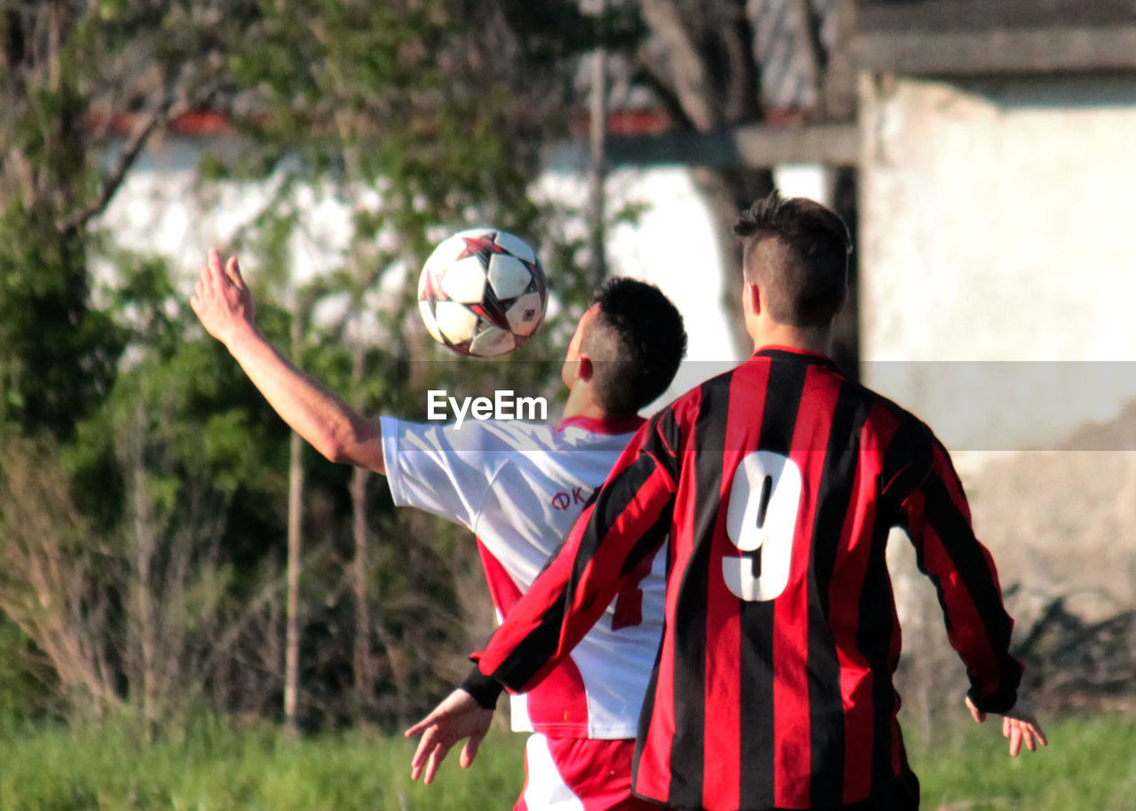waist up, sport, playing, rear view, red, soccer, boys, sports uniform, standing, real people, two people, soccer ball, leisure activity, soccer player, day, outdoors, sportsman, sports clothing, competitive sport, men, sports team, togetherness, soccer uniform, teamwork, tree, soccer field, athlete, young adult, adult, people