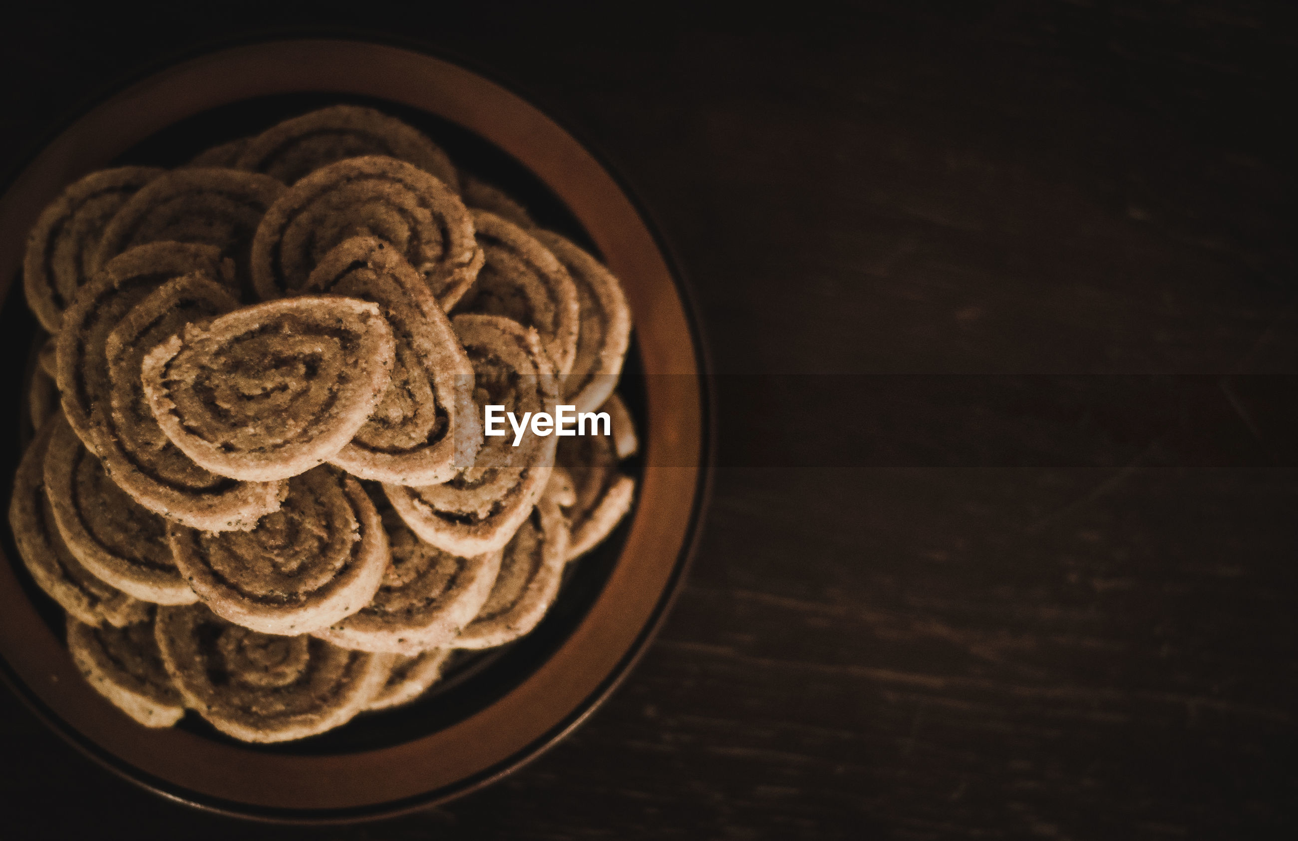 High angle view of cookies in bowl on wooden table