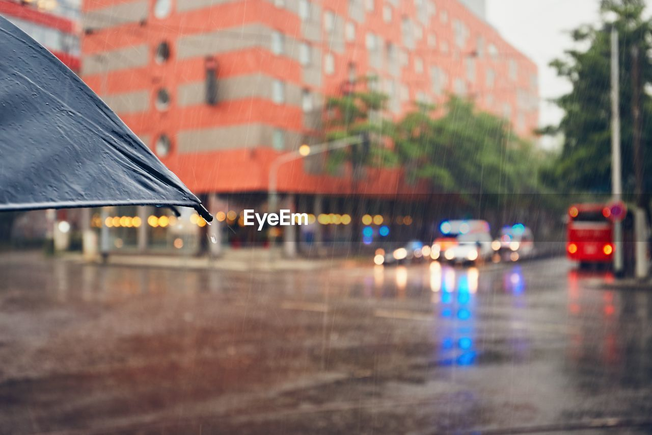 Cropped Image Of Umbrella On Street During Rainy Season