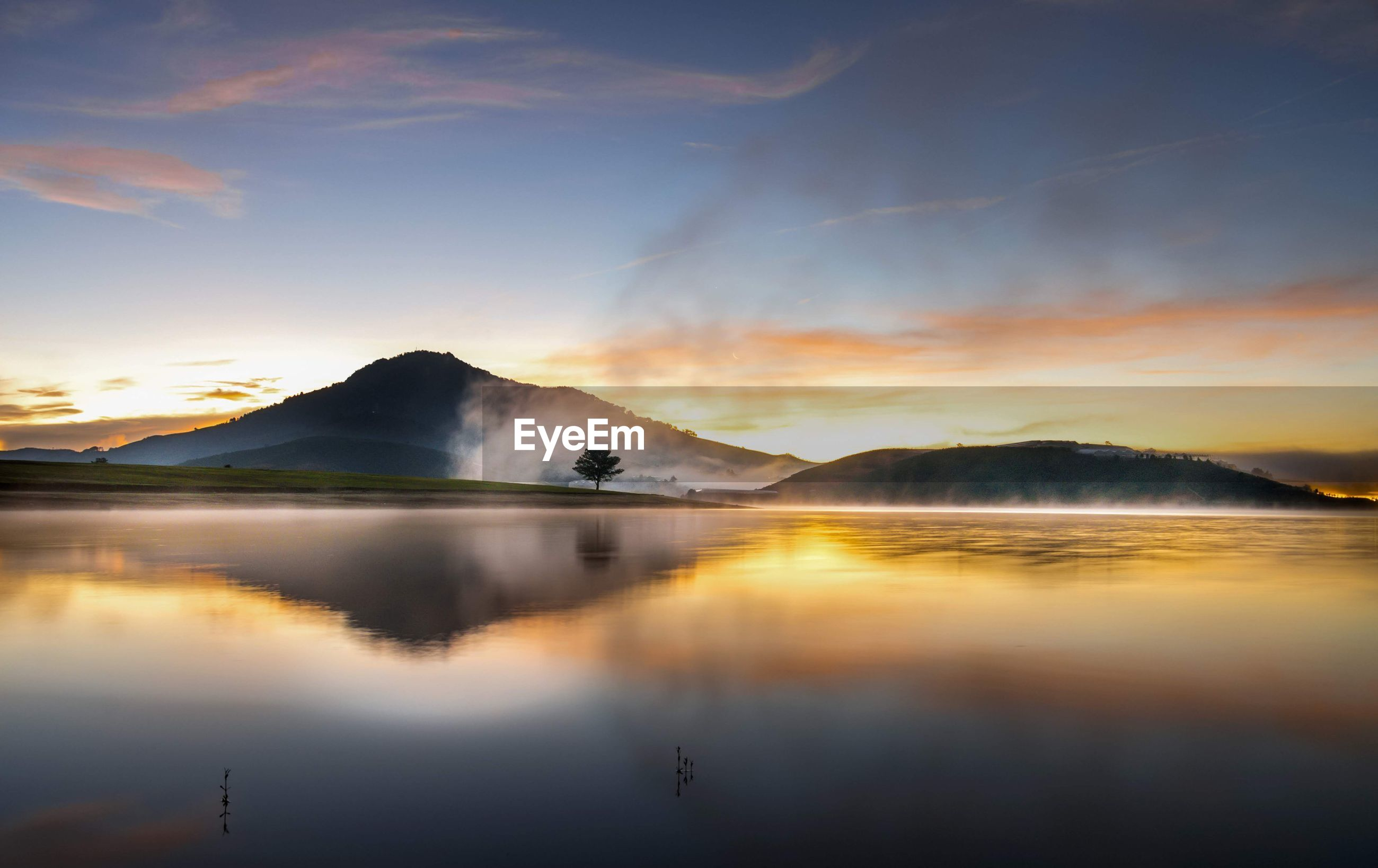 SCENIC VIEW OF LAKE BY MOUNTAIN AGAINST SKY DURING SUNSET