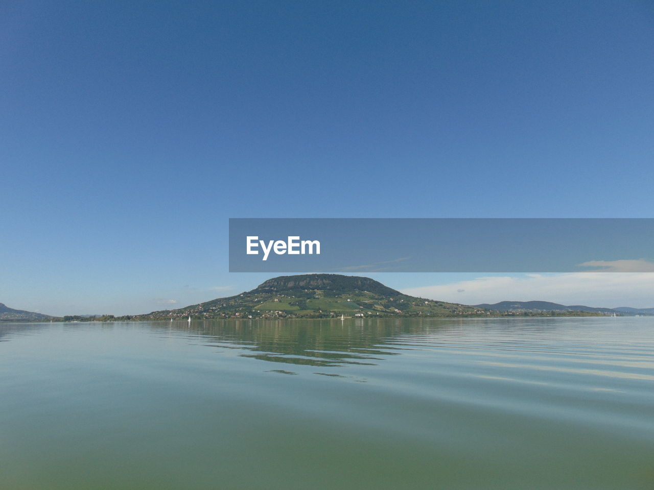 water, sky, tranquil scene, scenics - nature, tranquility, beauty in nature, copy space, waterfront, blue, mountain, nature, no people, idyllic, clear sky, lake, day, non-urban scene, reflection