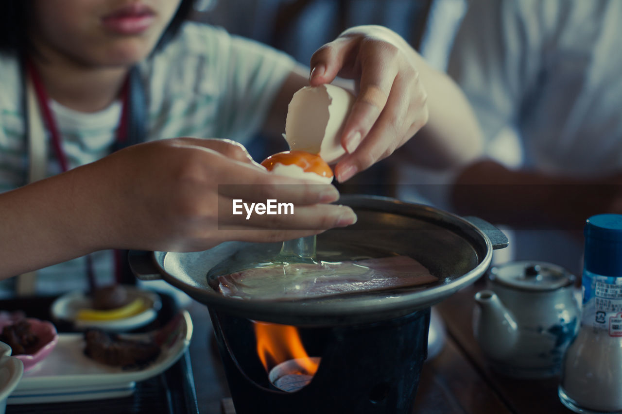 Person Cooking Egg In Cooking Pan