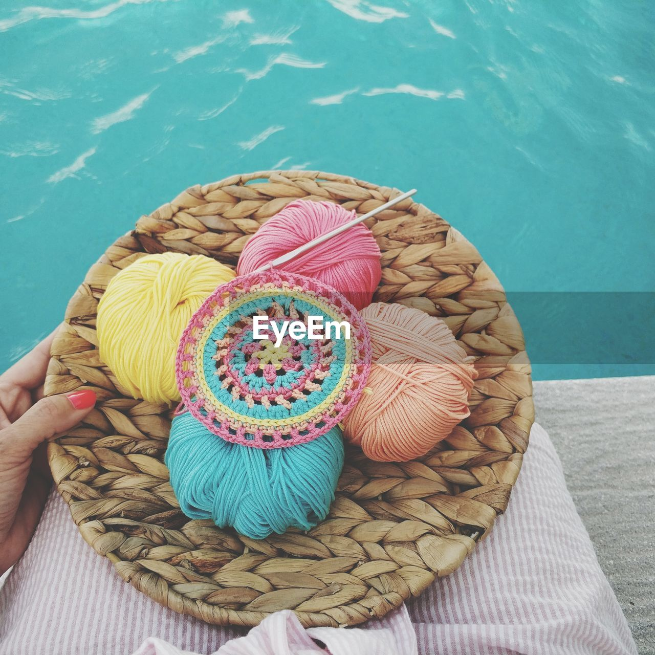 Midsection Of Woman Holding Wools In Container While Sitting At Poolside