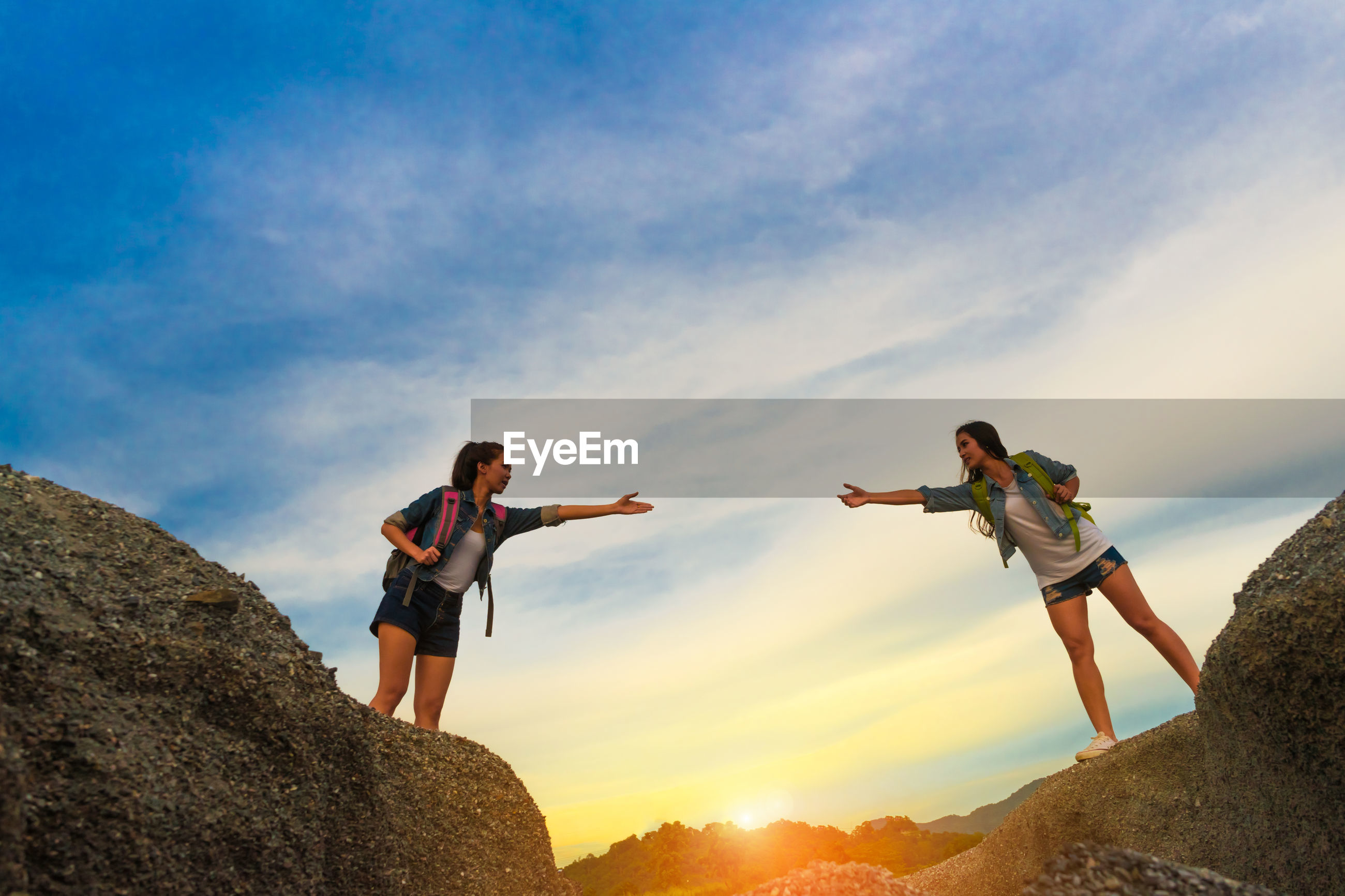 Female friends standing on rock against sky during sunset
