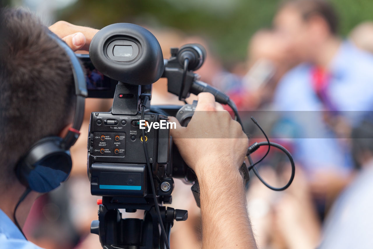 Rear view of man operating camera during event
