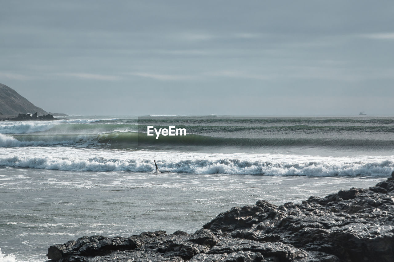 sea, water, wave, sky, motion, beauty in nature, scenics - nature, sport, aquatic sport, land, beach, surfing, horizon, day, nature, rock, horizon over water, cloud - sky, outdoors, power in nature, flowing water