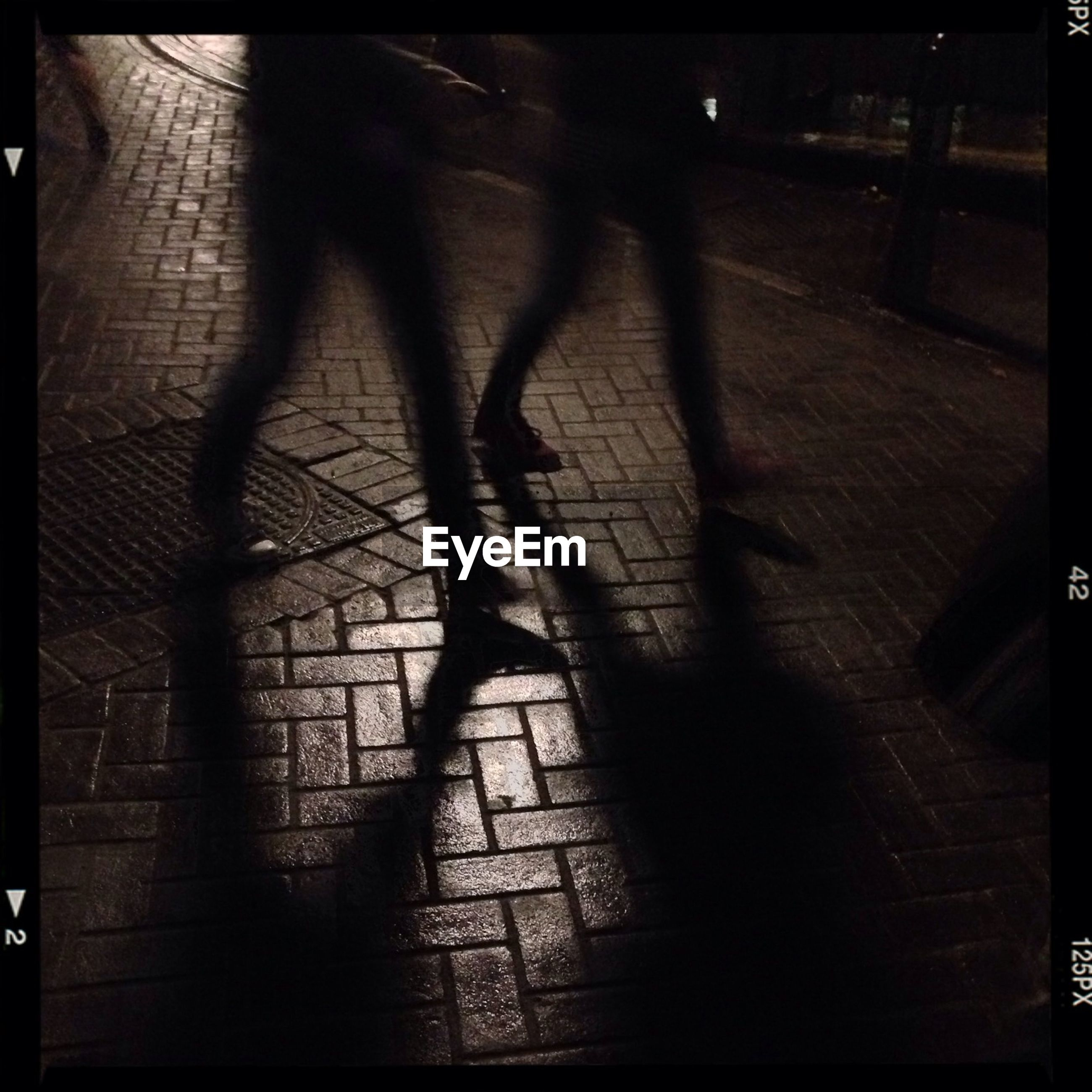 Low section of people walking on street at night