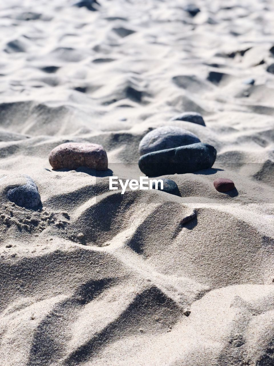 sand, beach, land, nature, day, no people, sunlight, water, close-up, solid, sea, rock, beauty in nature, tranquility, outdoors, sport, high angle view, stone - object, focus on foreground, pebble