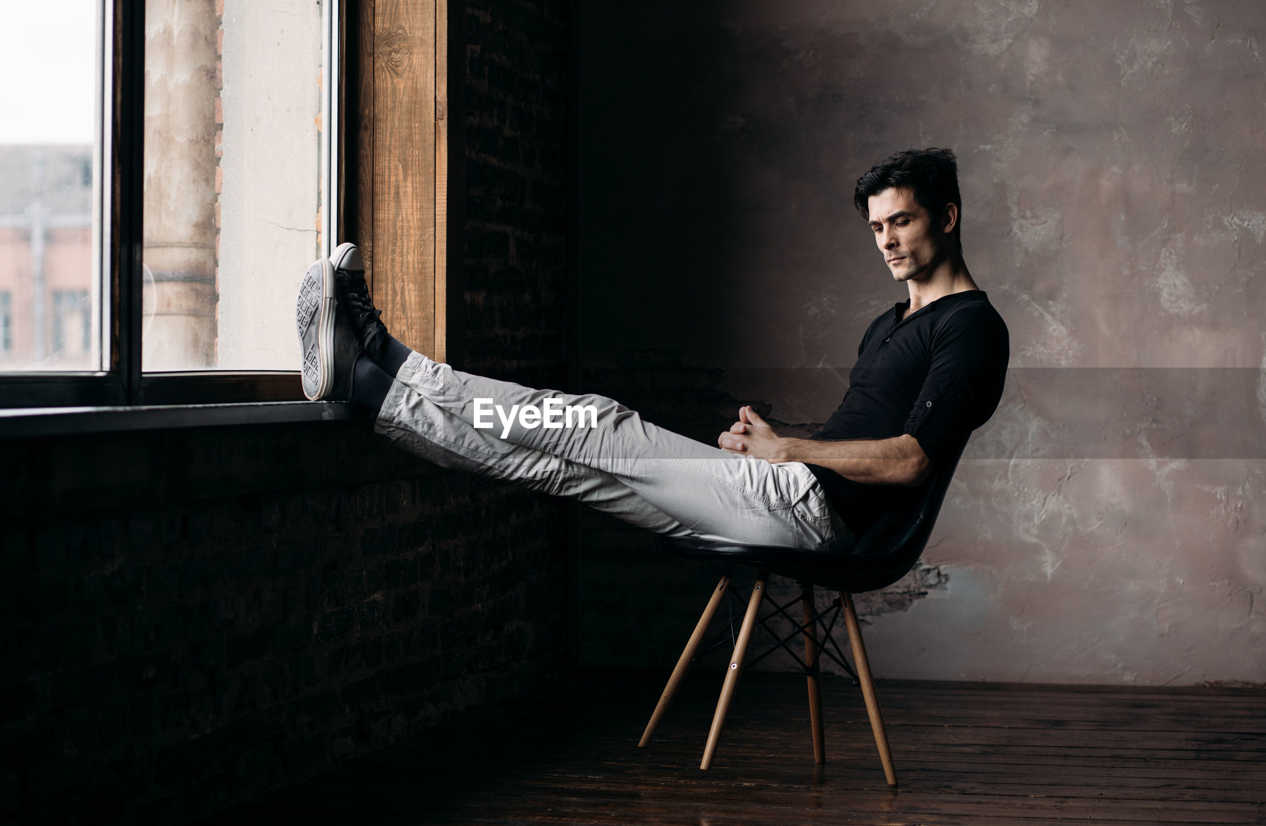 Young man relaxing on chair by wall