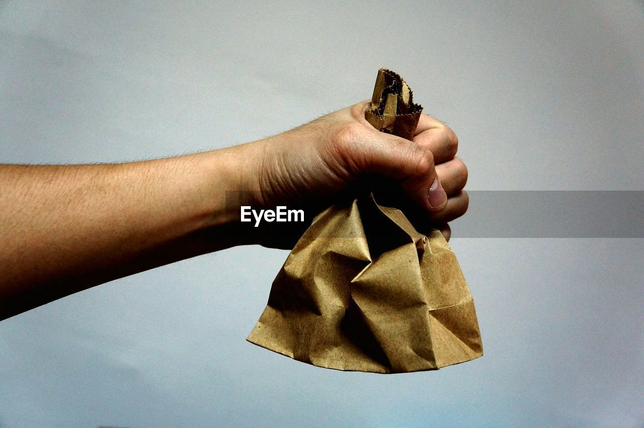 Close-up of cropped hand holding brown paper bag