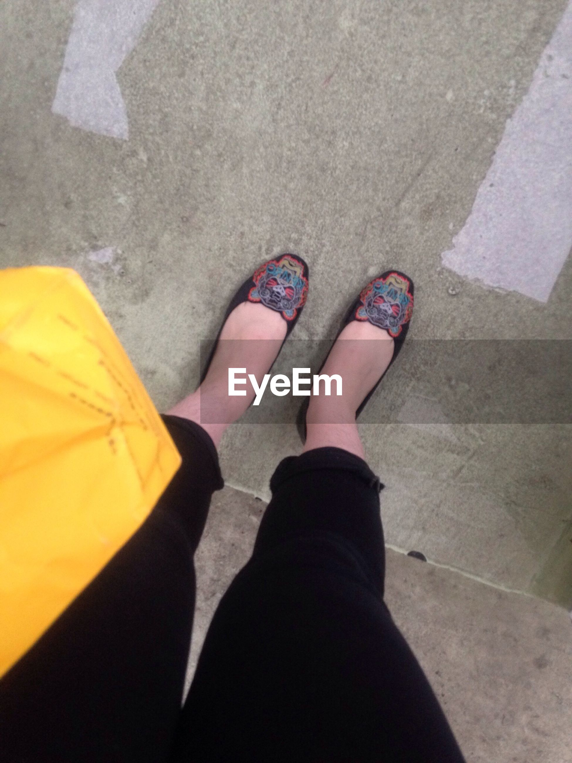 low section, person, personal perspective, high angle view, lifestyles, shoe, standing, human foot, street, leisure activity, footwear, men, unrecognizable person, jeans, directly above, tiled floor