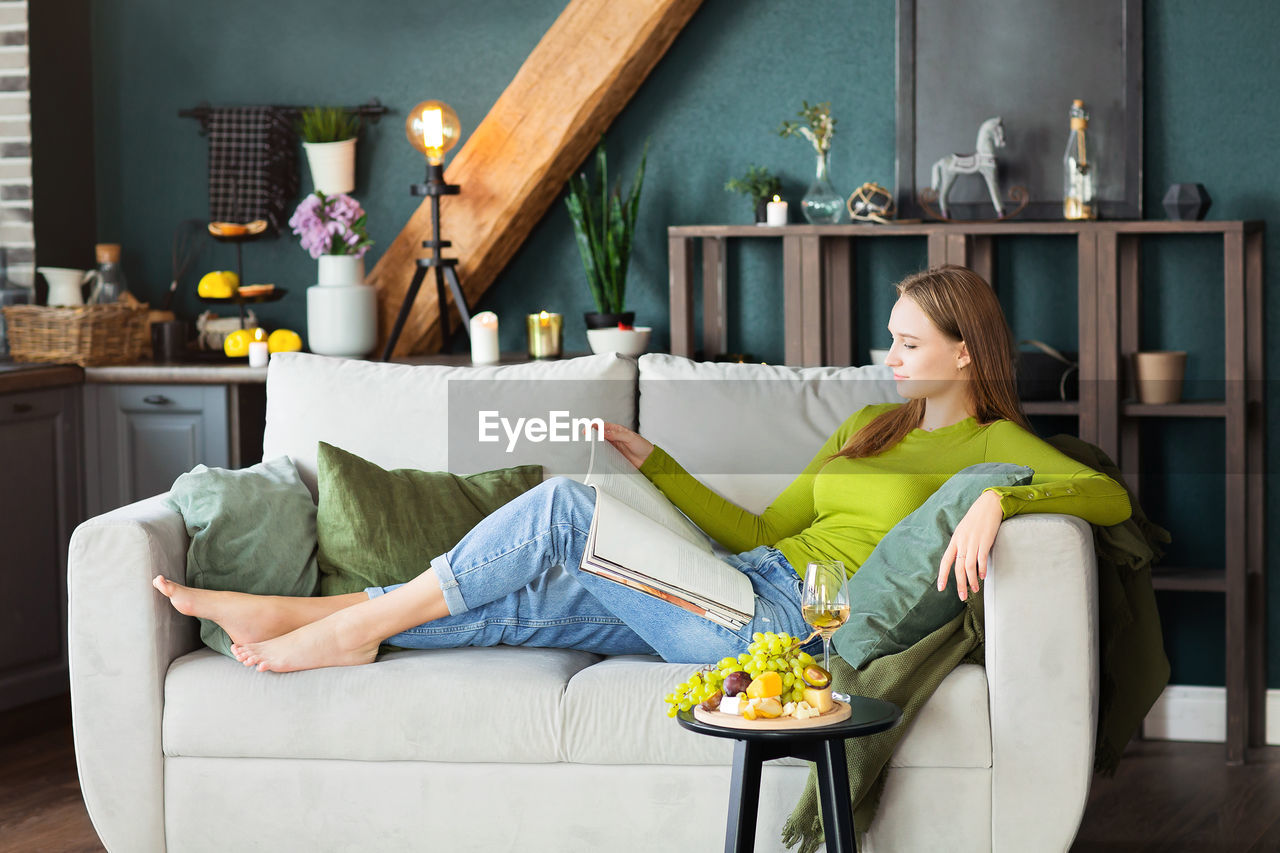 MIDSECTION OF WOMAN SITTING ON SOFA AT HOME