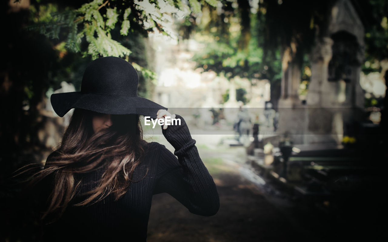 Woman With Long Hair Wearing Hat At Cemetery