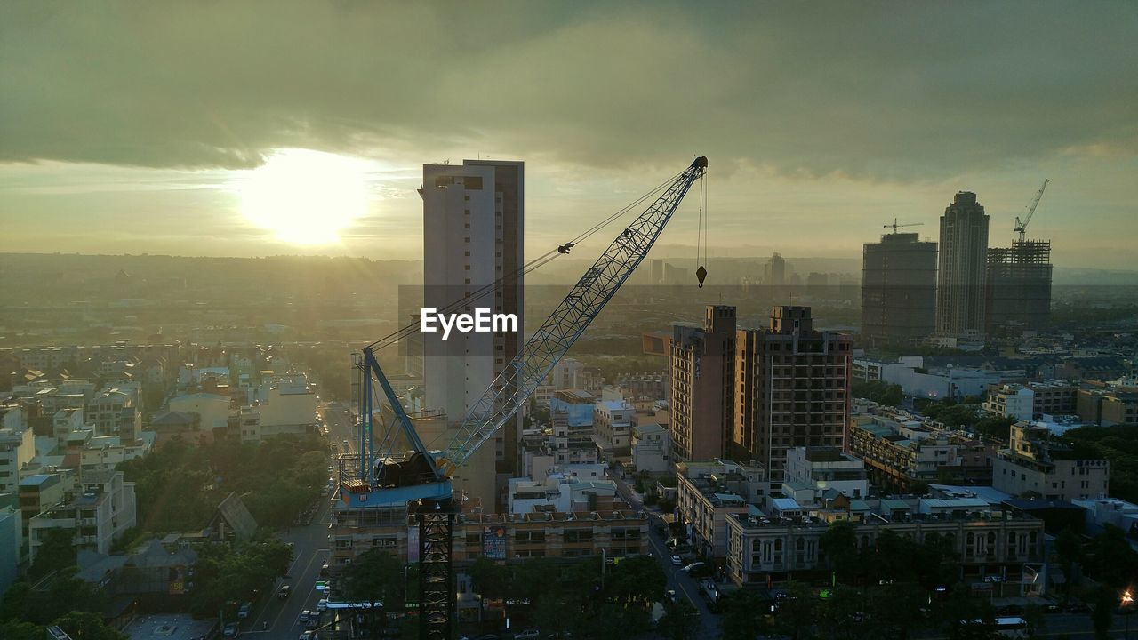 Crane And Buildings In City During Sunset