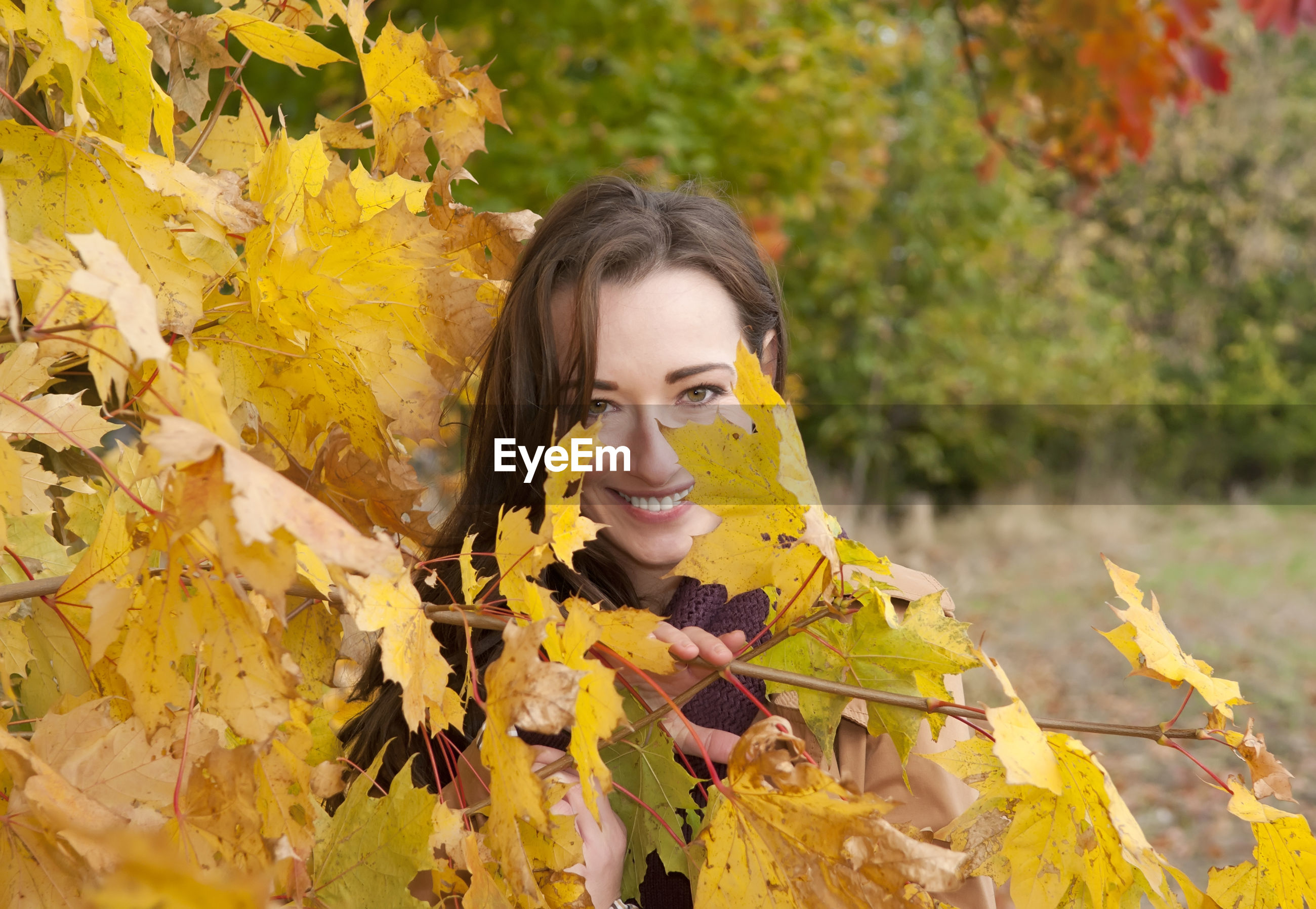 Portrait of woman wearing coat standing by trees in park during autumn