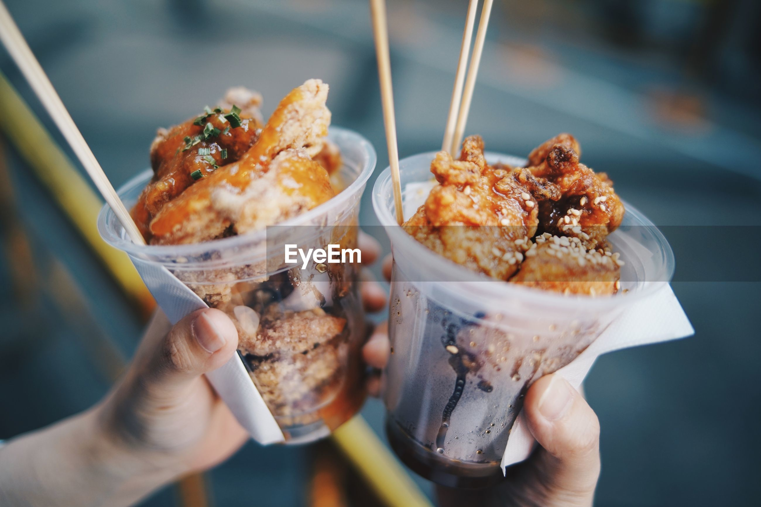 Close-up of hand holding food in disposable glasses outdoors