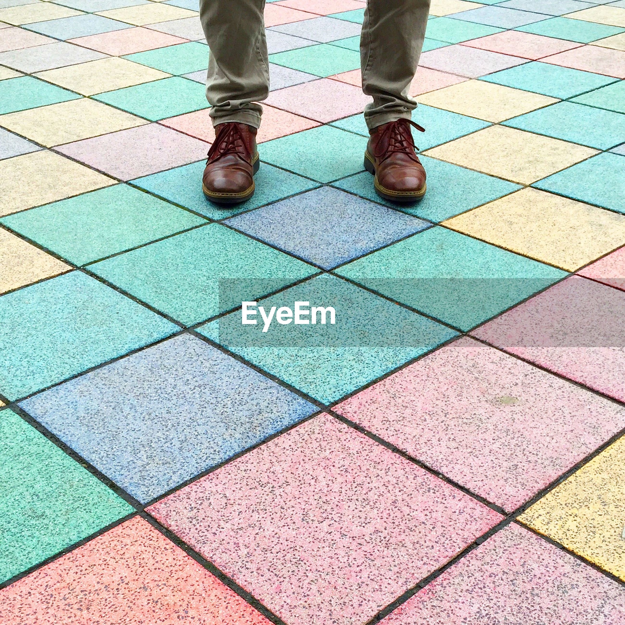 Low section of man standing on colorful paved walkway