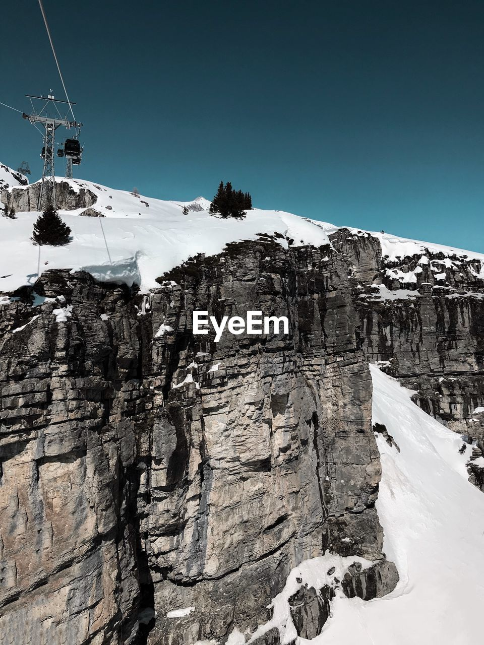 cold temperature, snow, winter, nature, mountain, beauty in nature, day, low angle view, outdoors, weather, scenics, rock - object, clear sky, tranquil scene, sky, tranquility, cliff, rocky mountains, no people, snowcapped mountain, ski lift