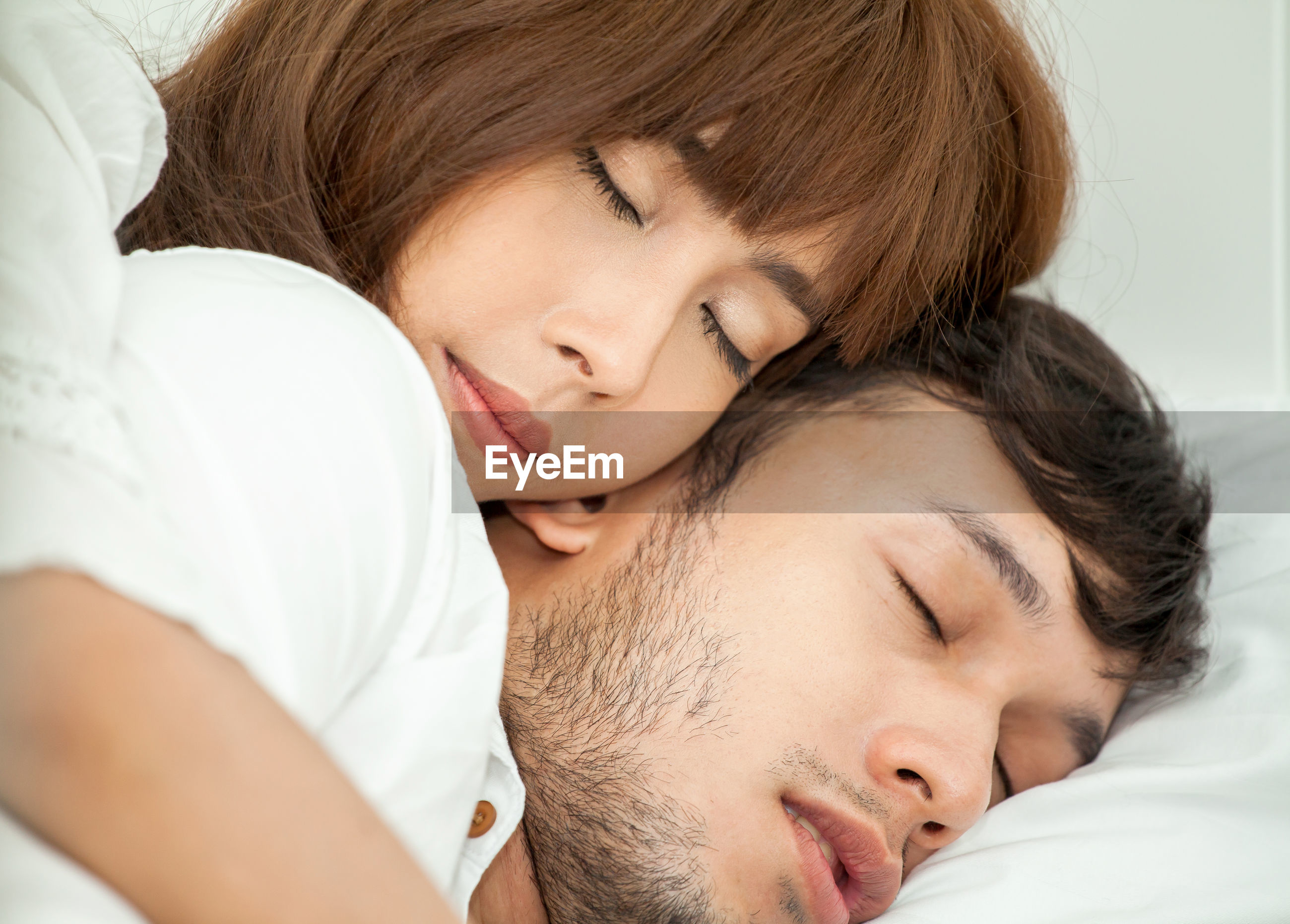 Close-up of couple sleeping on bed