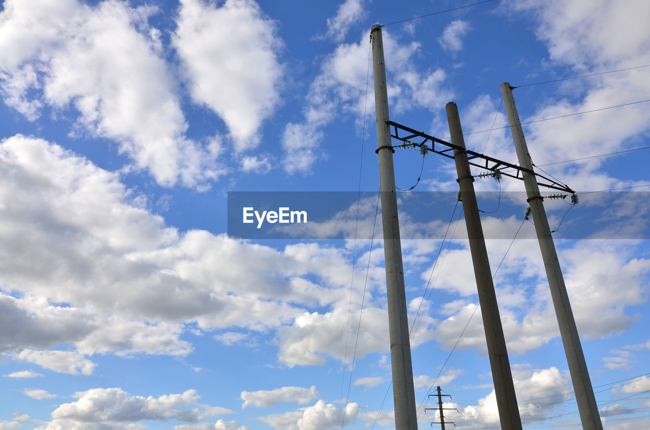 cloud - sky, sky, low angle view, nature, no people, day, outdoors, technology, beauty in nature, metal, blue, connection, communication, fuel and power generation, pole, tall - high, architecture, built structure, antenna - aerial, tranquility, power supply