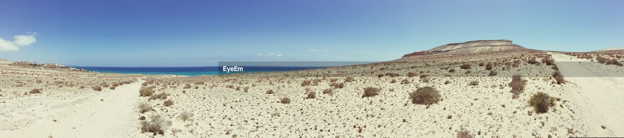 nature, scenics, tranquility, tranquil scene, beauty in nature, outdoors, sky, day, landscape, non-urban scene, sunlight, no people, blue, sand, mountain, beach, arid climate, sea, sand dune