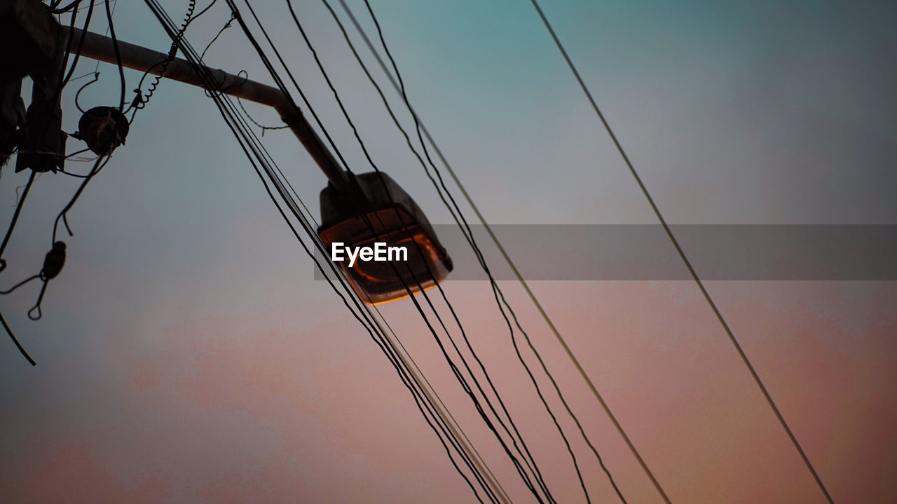 low angle view, sky, cable, sunset, nature, rope, no people, hanging, outdoors, connection, transportation, orange color, sailboat, day, metal, mode of transportation, electricity, power line, pole, cloud - sky, power supply