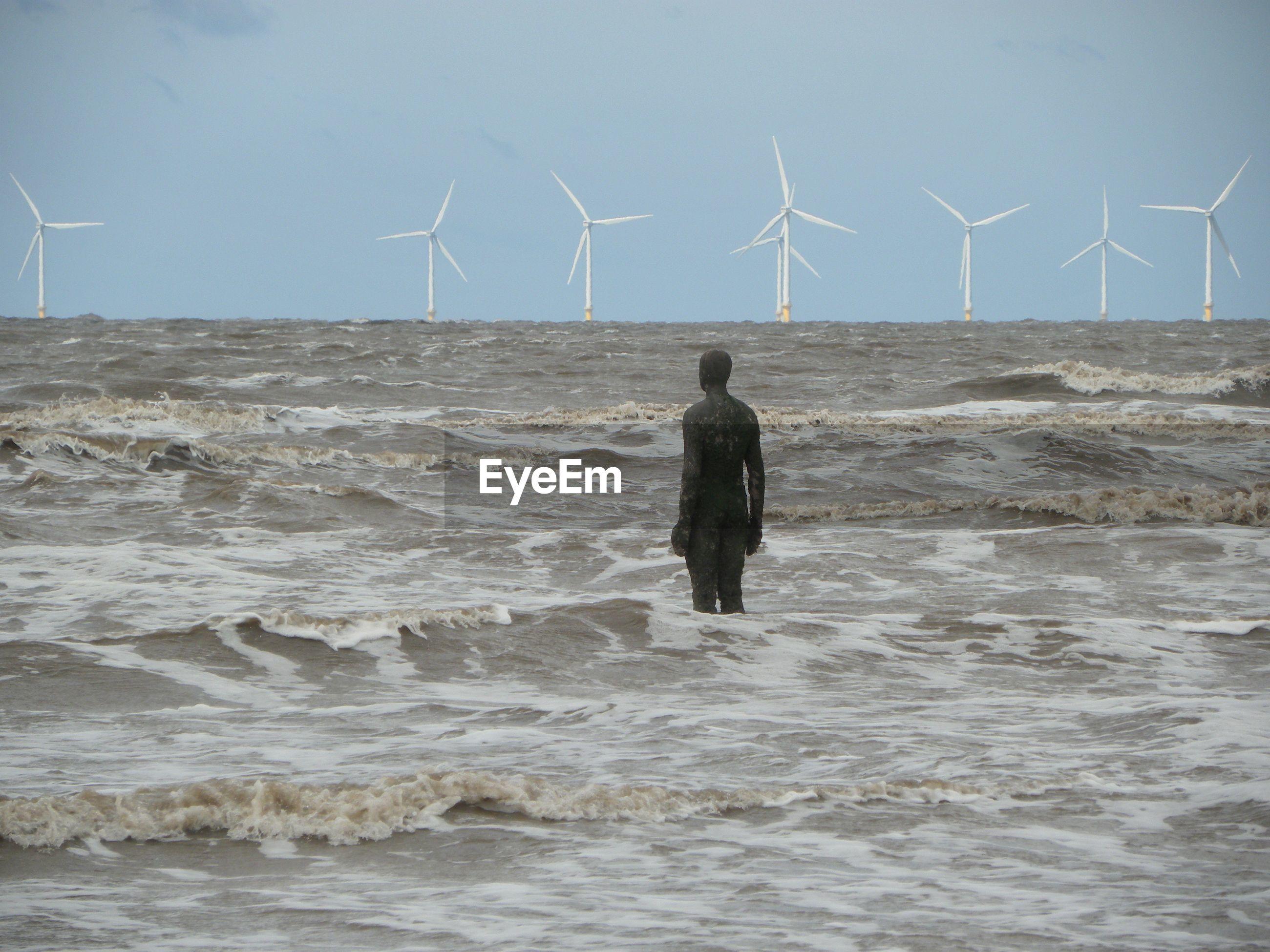 Metallic ironman in sea against wind turbines at crosby beach
