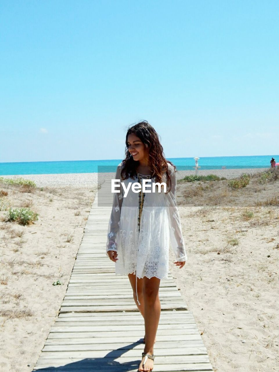 Young Woman Walking On Beach Against Clear Sky
