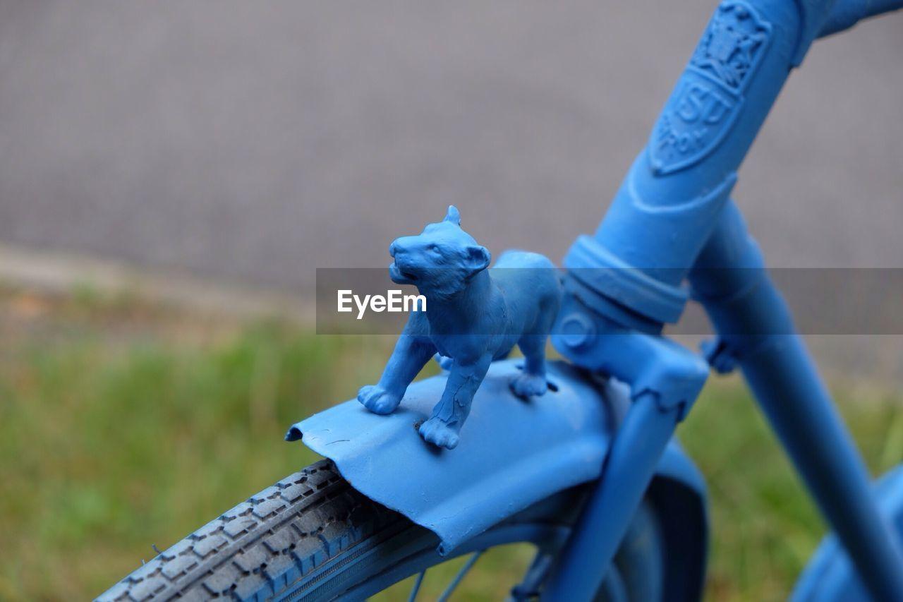 Animal figurine on blue bicycle
