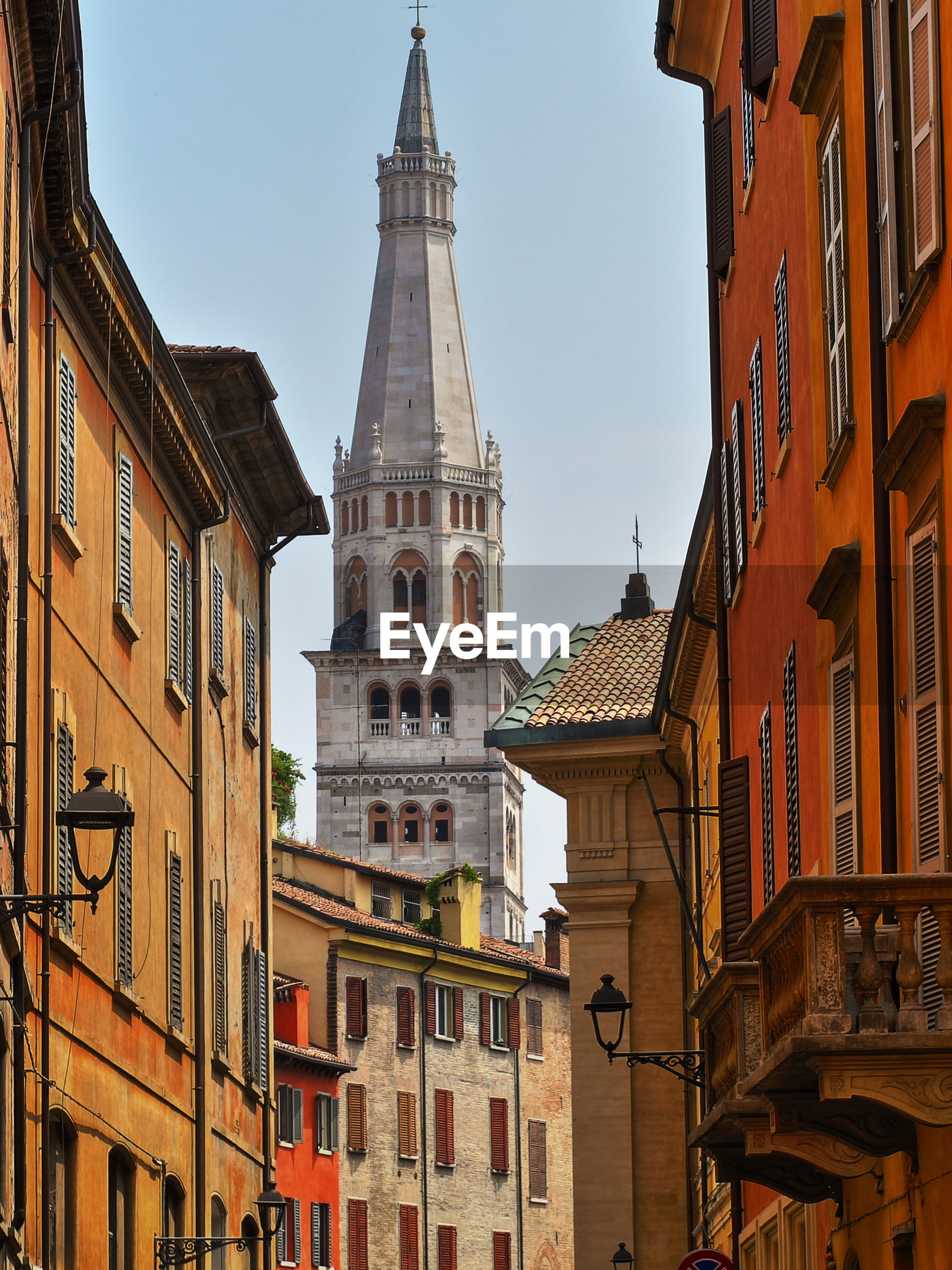 Modena tower bell named ghirlandina between buildings against clear sky