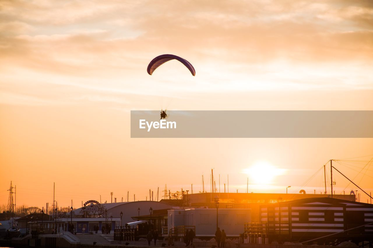 sky, sunset, extreme sports, orange color, cloud - sky, transportation, parachute, sport, mid-air, nature, flying, adventure, sun, beauty in nature, paragliding, built structure, architecture, building exterior, mode of transportation, city, outdoors