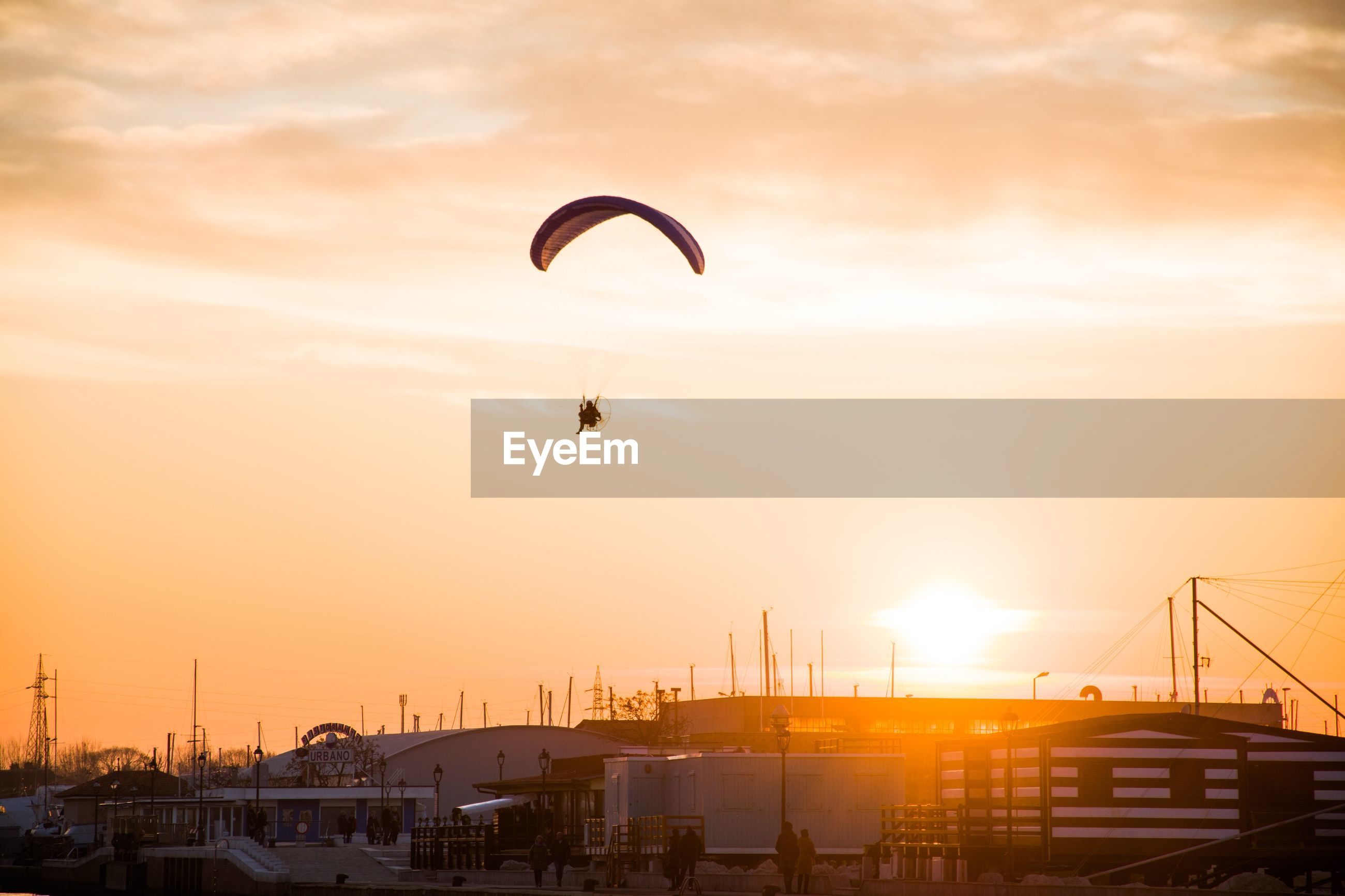 Person paragliding over city against sky during sunset