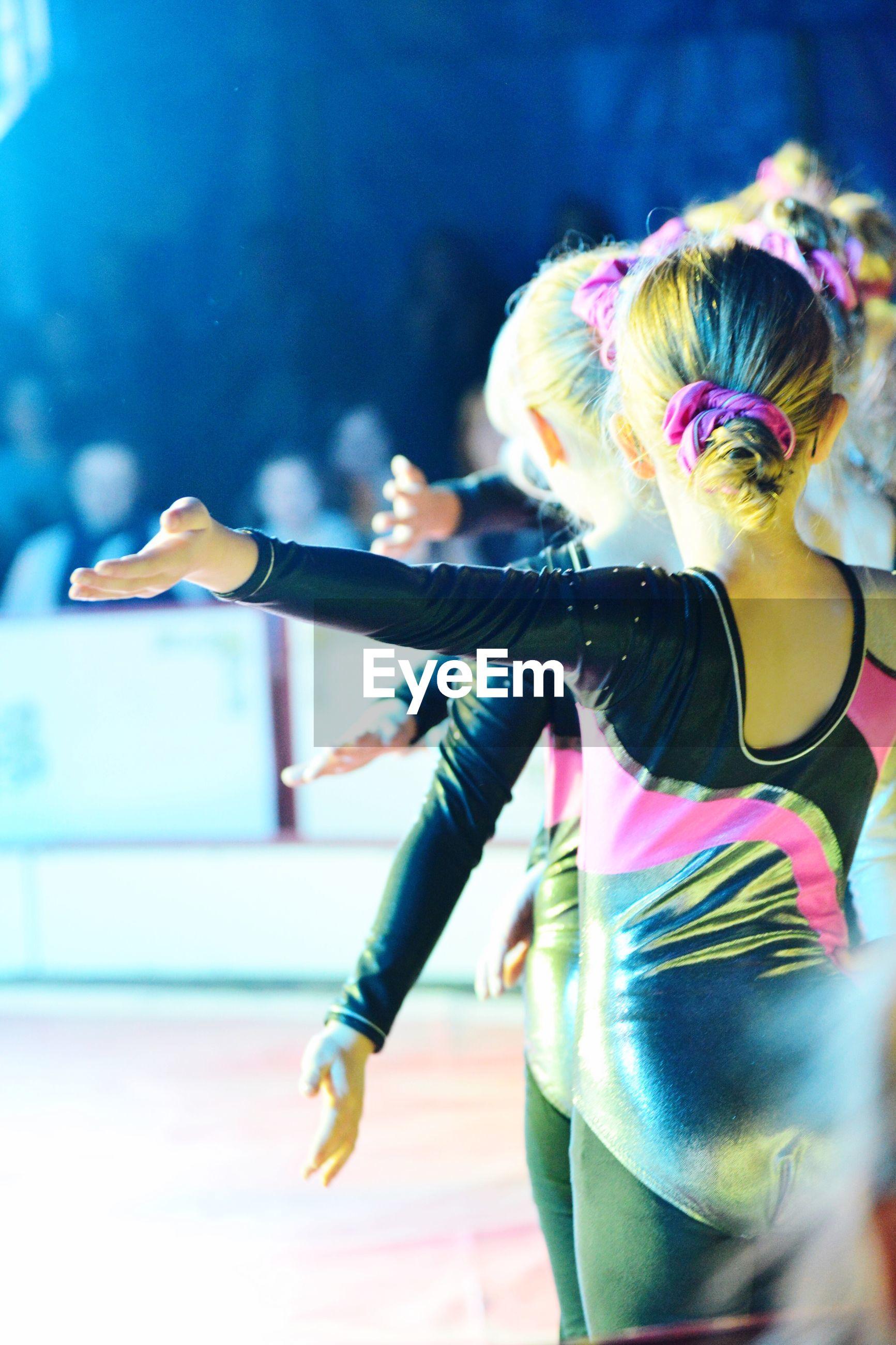 FULL LENGTH REAR VIEW OF WOMAN DANCING AT NIGHTCLUB
