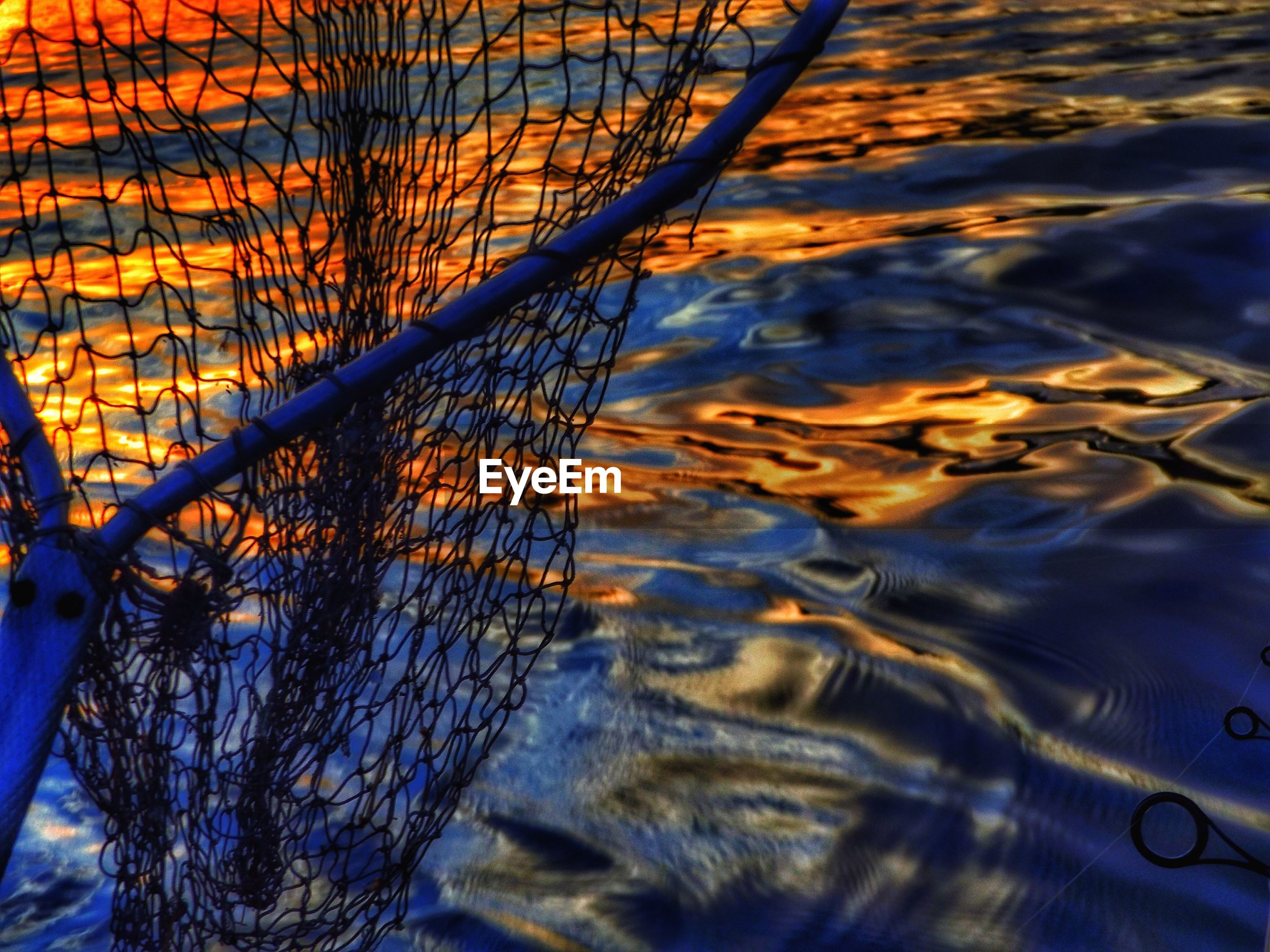 Close-up of fishing net against water