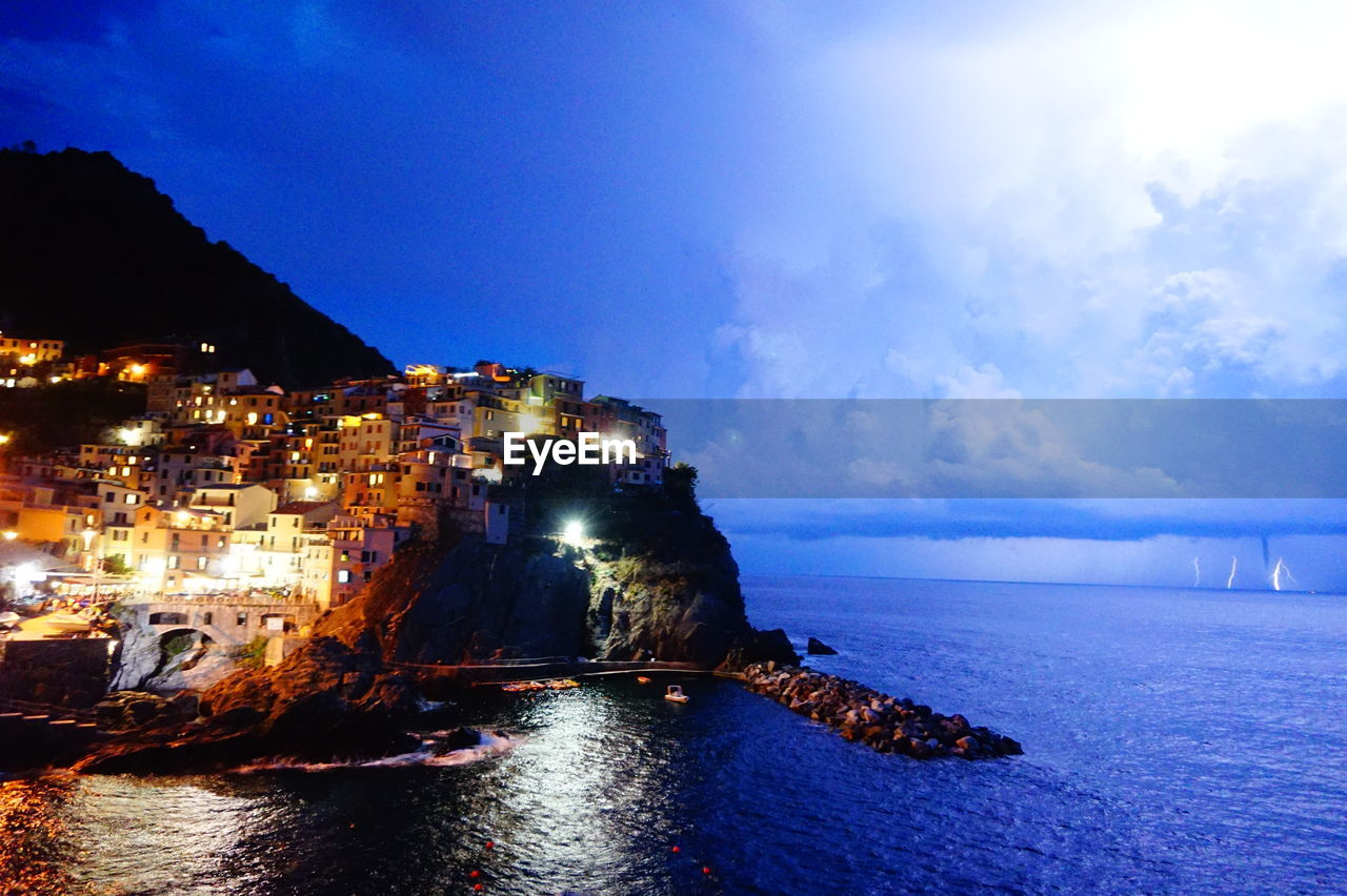 SCENIC VIEW OF SEA AGAINST ILLUMINATED BUILDINGS IN CITY