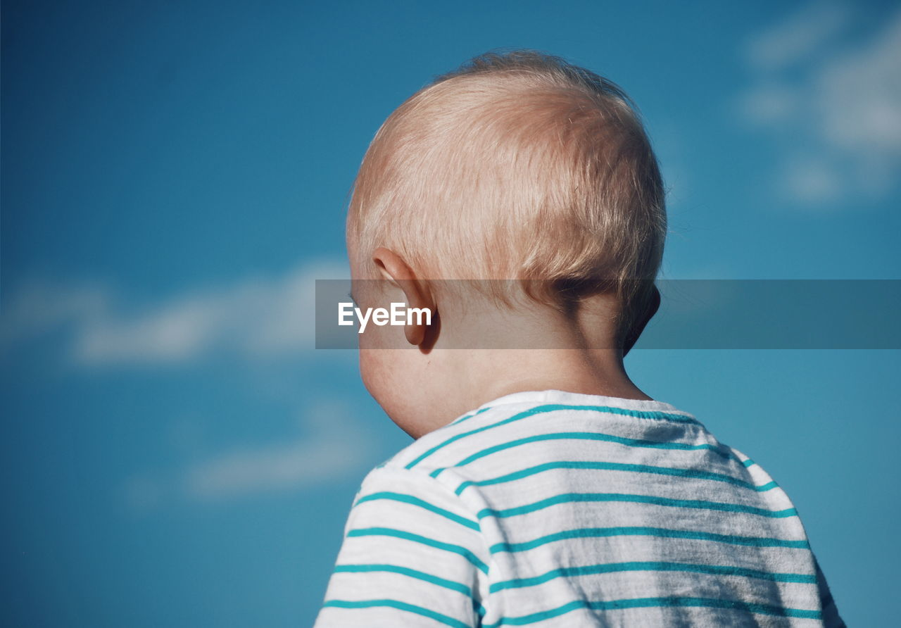 Close-up of boy against blue sky