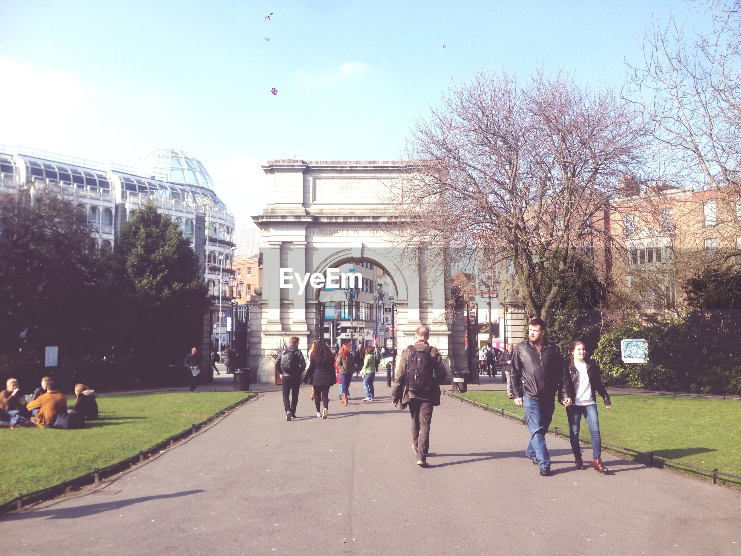 large group of people, men, person, architecture, walking, built structure, building exterior, lifestyles, sky, tree, leisure activity, city, city life, mixed age range, grass, full length, day, footpath, the way forward